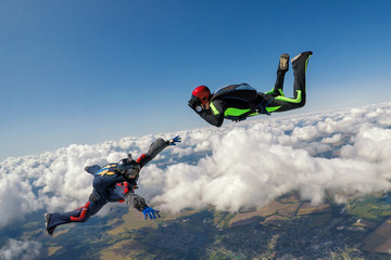 Two skydivers over the clouds during freefall