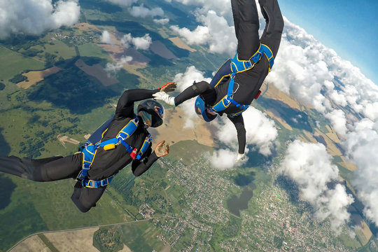 Two skydivers free falling over the clouds