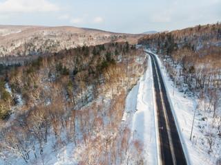 Aerial view of a road cutting through the mountain between Otaru and Niseko in Hokkaido, Japan
