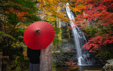 Wall Mural - Pre wedding photo for Japanese couple and red umbrella on the red bridge in minoh waterfallrfall park with autumn red and yellow background