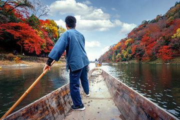 Wall Mural - Boat taxi service in arashiyama river with autumn  background