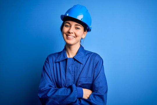 Young beautiful worker woman with blue eyes wearing security helmet and uniform happy face smiling with crossed arms looking at the camera. Positive person.
