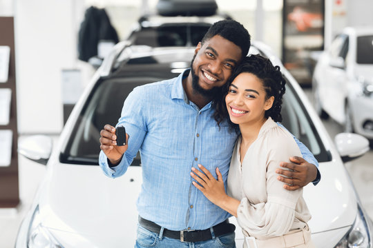 African American Couple Showing Car Key Standing In Automobile Showroom