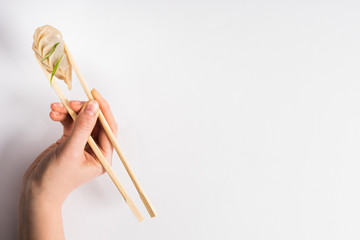 cropped view of woman holding delicious Chinese boiled dumpling with chopsticks on white background