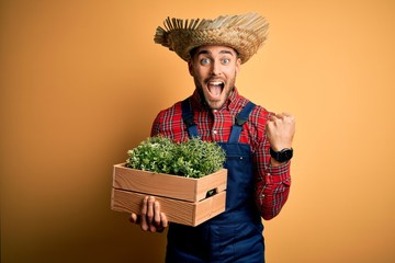 Young rural farmer man wearing countryside hat holding green organic plant from harvest screaming proud and celebrating victory and success very excited, cheering emotion Fotomurales