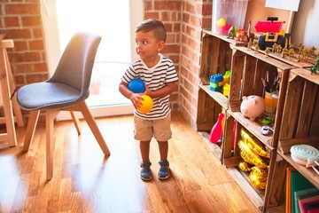 Beautiful toddler boy playing with colored small balls at kindergarten