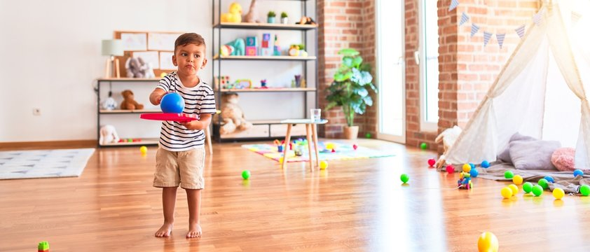 Beautiful toddler boy playing tennis with red racket and ball at kindergarten