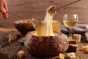 cheese fondue in bread bowl with wine