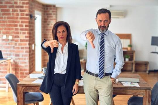 Two middle age business workers standing working together in a meeting at the office looking unhappy and angry showing rejection and negative with thumbs down gesture. Bad expression.
