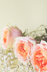 Floral arrangement of roses and small white flowers.