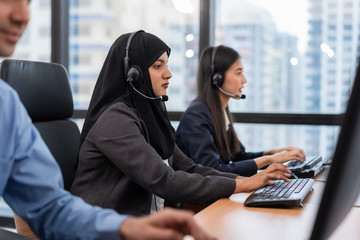 Arabian or Muslim woman works in a call center operator and customer service agent wearing microphone headsets working on computer in a call , talking with customer for assisting