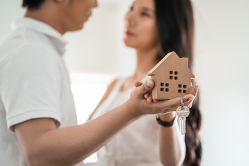 Happy smiling asian couple holding a model house, and danceing together with feeling happiness. Young loving couple with small wooden house new home concept