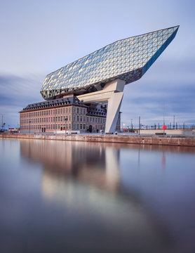 ANTWERP-JULY 19, 2019. Port House Antwerp at dusk. Zaha Hadid Architects added a glass extension to a renovated fire station. With a total of 12,800 square meters the headquarters houses a 500 staff.