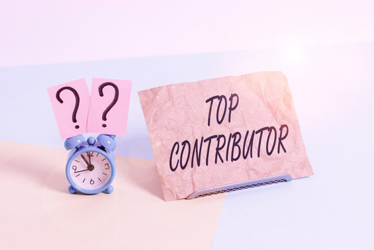 Word writing text Top Contributor. Business photo showcasing demonstrating who is knowledgeable in a particular category Mini size alarm clock beside a Paper sheet placed tilted on pastel backdrop