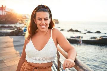 Beautiful young woman walking on beach promenade enjoying ocean view smiling happy on summer vacation Wall mural