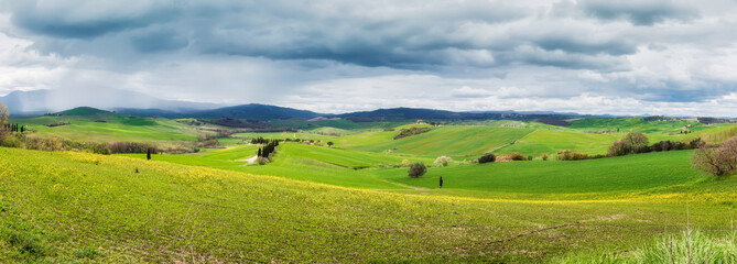 Amazing Tuscany landscape with green rolling hills in spring rainy morning