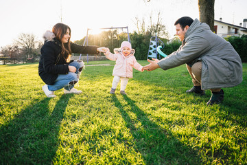 Happy family at the park - Mom and dad walking with their child in a park at sunset holding her hand and helping her learn to walk alone - Mother and father with their daughter in a moment of intimacy