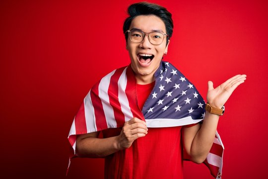 Young chinese patriotic man wearing united states of america flag over red background very happy and excited, winner expression celebrating victory screaming with big smile and raised hands