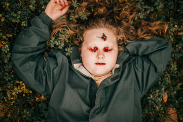 Portrait of pretty chubby girl with forest berries on her face lies on a grass
