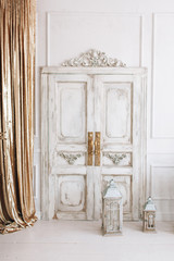 beautiful  light interior. classic room with wooden floor white walls with moldings, dressing  table with mirror decorated with elements, chair, sofa, lanterns, gold curtains vintage old door