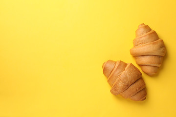 Baked croissants on yellow background, top view