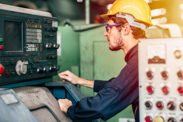 young profession technician engineer operate heavy machine to automated CNC in factory.