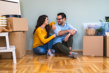 Happy couple sitting on the floor of empty apartment. Move in to new home. Stock photo