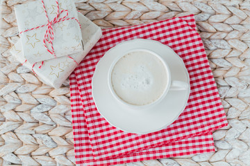 A cup of coffee or cappuccino and two gift boxes on white background.