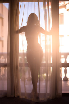Sexy slim dark silhouette of a young woman against the background of a window with curtains and sun rays