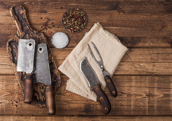 Vintage hatchets for meat on wooden chopping board with salt and pepper on wooden table background with linen towel and fork and knife. Top view Wall mural