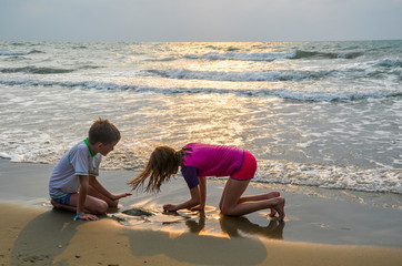 children playing on the sand in a Caribbean sea sunset