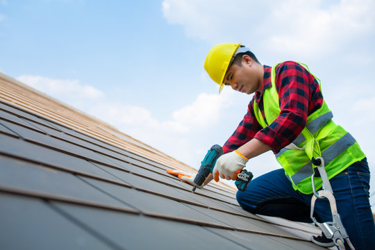 Construction workers Fixing roof tiles, with roofing tools, electric drills used on roofs in safety kits for safety.