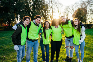 Group of friends together after a volunteer event for the collection of waste in a park at sunset - Millennial having fun together