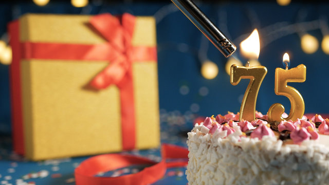 White birthday cake number 75 golden candles burning by lighter, blue background with lights and gift yellow box tied up with red ribbon. Close-up