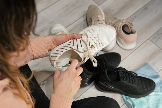 A woman sits on the floor and cleans sports shoes with a foam detergent, selective Focus, closeup.