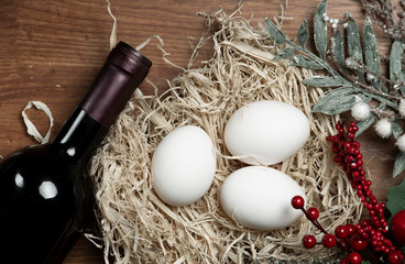 Wine red bottle and chicken eggs in hay.
