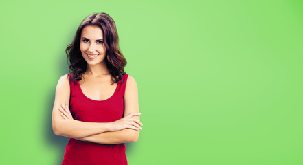 Young smiling woman in casual red clothing, in crossed arms pose. Green color wall background. Happy beautiful girl at studio. Brunette Model with long hair posing at studio picture.