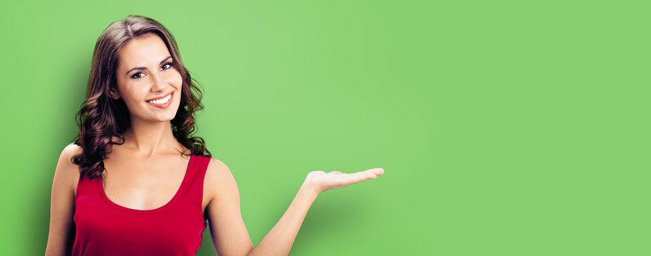 Happy smiling woman giving, holding or showing something or product or copy space for some text or slogan, green background. Brunette model in casual red clothing posing at studio.