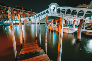 Venice, Italy. A night-time view of pier at iconic Rialto Bridge, spanning over the Grand Canal lit by city illumination