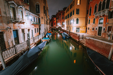 Venezia Italy. Narrow channel and gondola boats in lagoon city venice at night. Vivid colored old brick buildings around