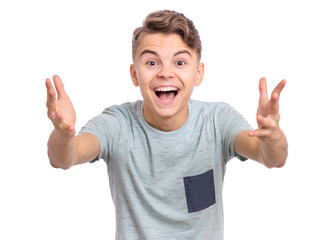 Portrait of joyful teen boy with raised hands. Handsome caucasian teenager laughing and screaming isolated on white background. Happy child exclaiming with joy and excitement, looking at camera.