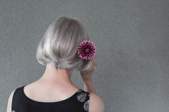 Gray-haired lady with red dahlia