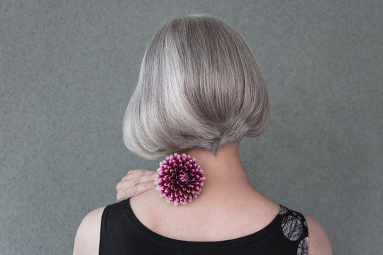 Lady with beautiful silver hair and red dahlia
