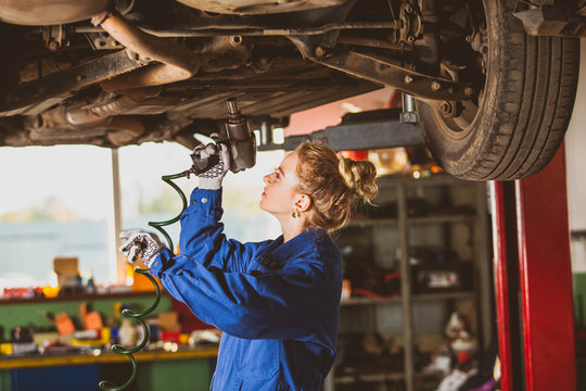 Young female mechanic works under the car