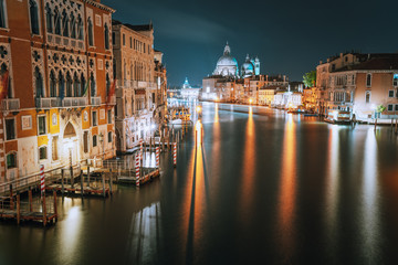 Venice, Italy. Grand Canal at night. Illumination light reflected on water surface. Majestic Basilica di Santa Maria della Salute in background