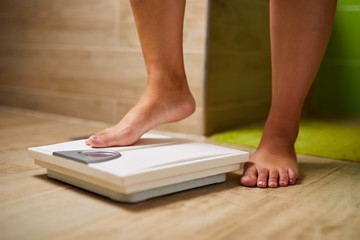 Feet of a woman on a weight scale while weighing