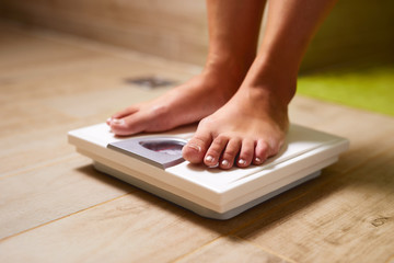 Woman standing on weight scale in bathroom