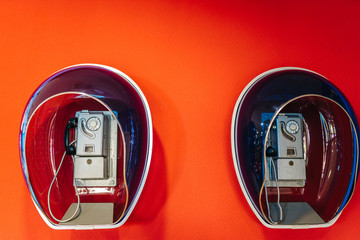 Public telephone from the seventies, hanging on a red wall