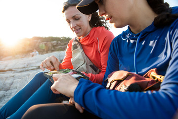 Two women looking at their fly selection while fly fishing on teh coast of Maine.