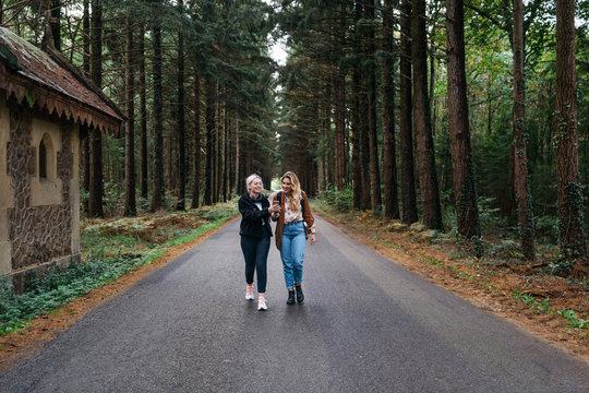 Two women walking on a road in the forest while watching their phone